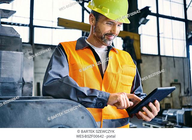 Smiling man wearing protective workwear using tablet in factory