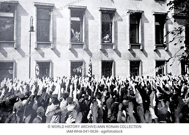 Nazi supporters gather to wave to Hitler as he looks from his office in the Chancellery in Berlin