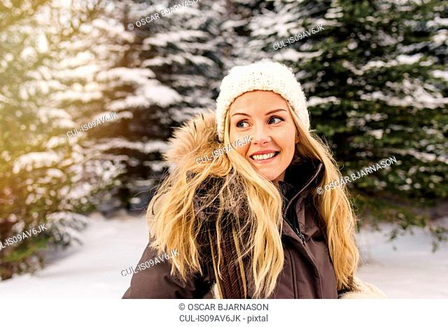 Mid adult woman in front of snow covered trees looking away smiling