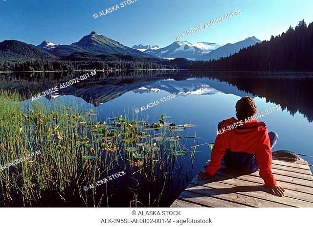 Man on dock Auke Lake Juneau Coast Mtns Southeast Alaska summer viewing