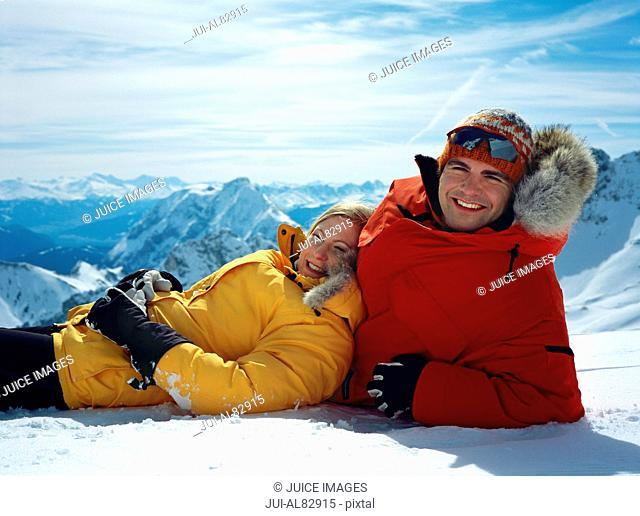 Couple laying in snow with mountains in background