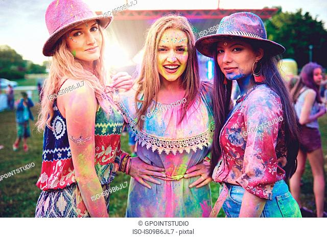 Portrait of three young boho women covered in coloured chalk powder at festival
