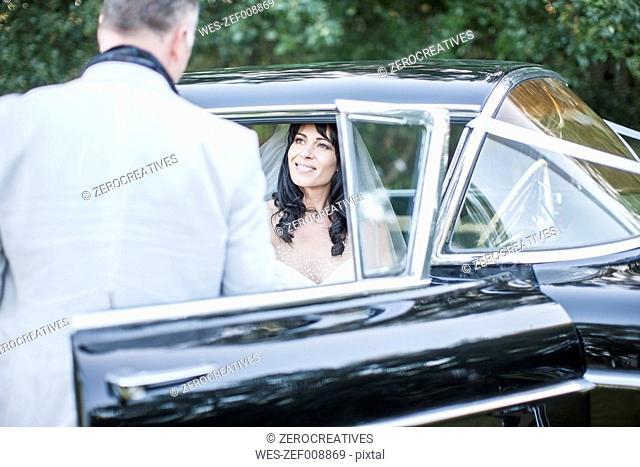 Bride and groom sitting in vintage car