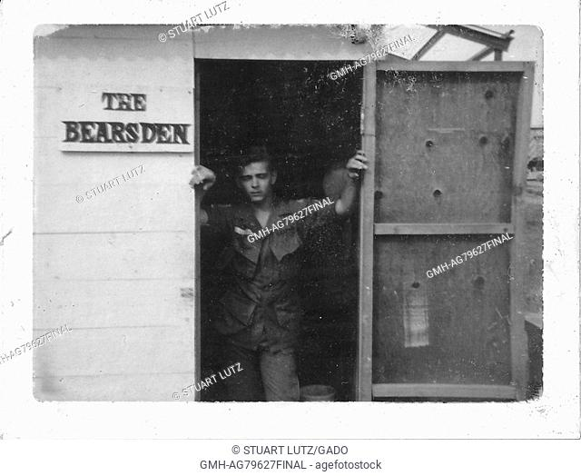 A United States Army serviceman in uniform standing in the doorway of a wooden building, there is a sign on the exterior of the building that reads 'The Bears...