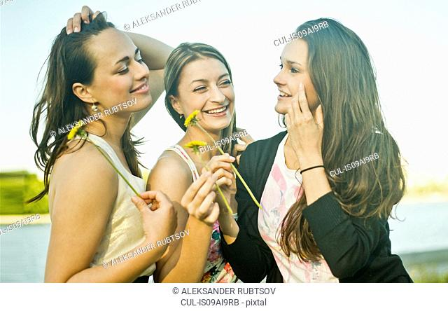 Three young female friends on riverbank holding dandelions