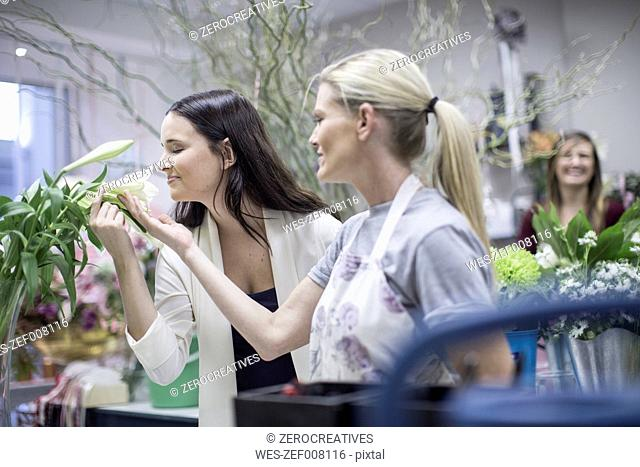 Shop assistant with woman in flower shop smelling at blossom