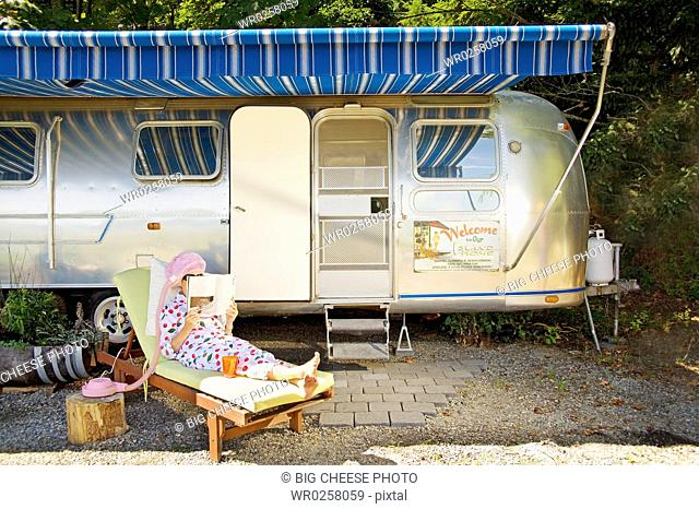 Woman reading in front of motor home