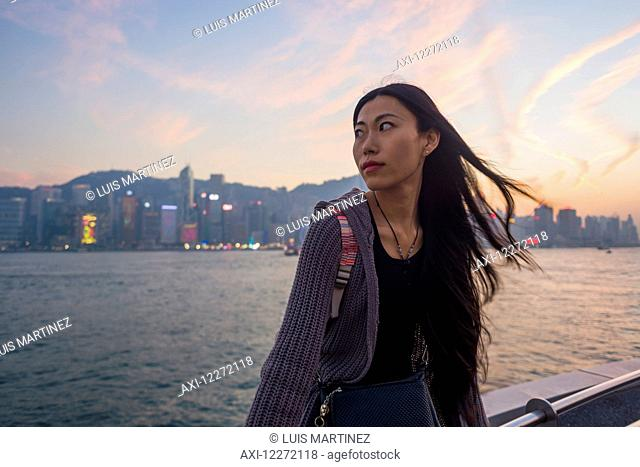 A young woman at the waterfront sitting on the railing at sunset with the skyline in the background, Kowloon; Hong Kong, China