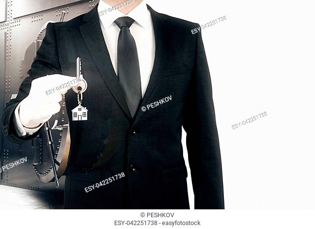 Businessman holding key with house keychain on silver bank vault background. Property purchase concept