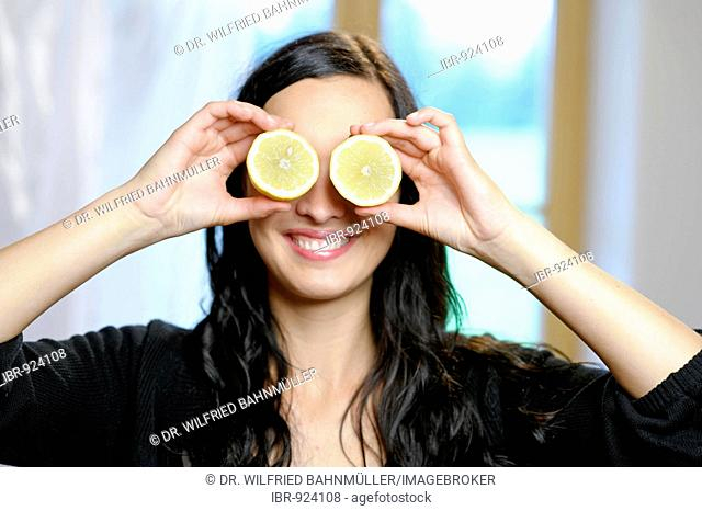 Young women holding slices of lemon in front of her eyes, vitamin C