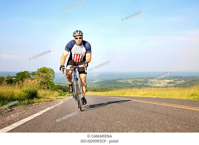 Man cycling on open road