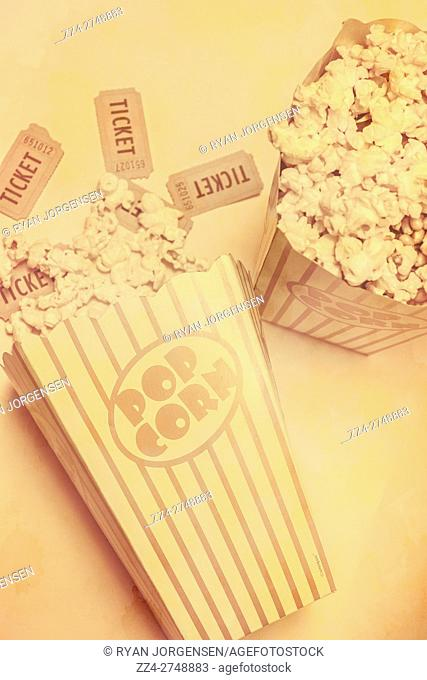 Old style retro popcorn containers fill with movie theatre stubs and buttered pop corn. Classical Hollywood cinema