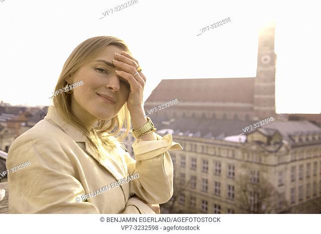sensual blogger woman on balcony next to church Frauenkirche, Marienkirche, in Munich, Bavaria, Germany