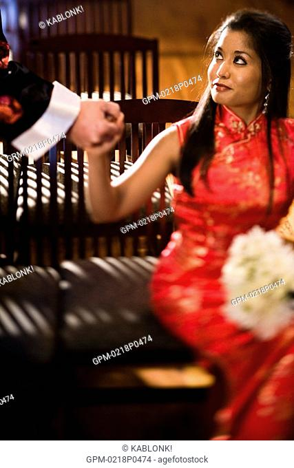 Young Asian woman in traditional dress holding outstretched hand of man, selective focus