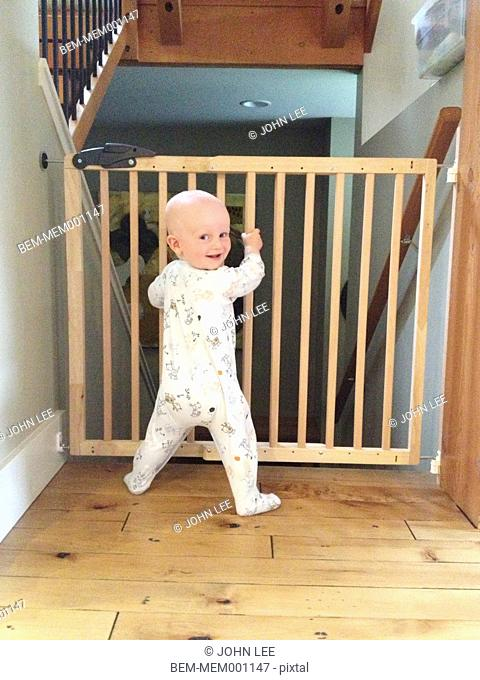 Caucasian baby standing at safety gate