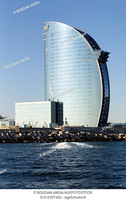 """Barcelona - iconic """"""""Hotel W"""""""" reflecting light in the form of the letter """"""""W"""""""" on the Mediteranean Sea waves at dusk"""