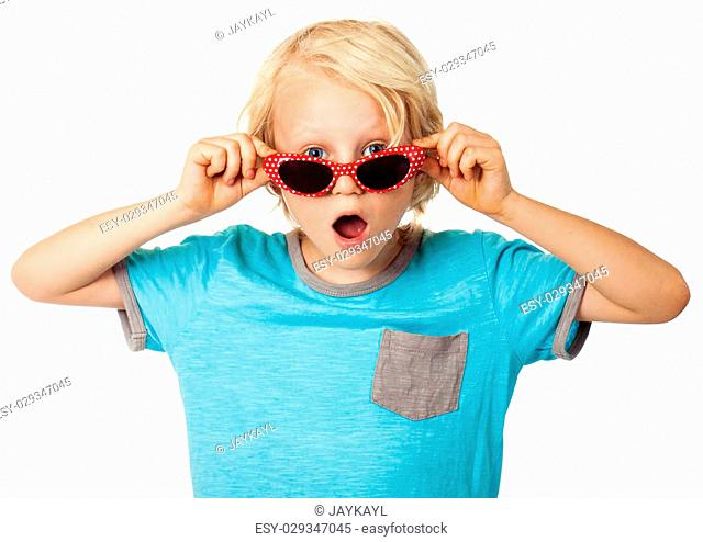 A cute surprised young boy looking over his sunglasses at the camera. Isolated on white