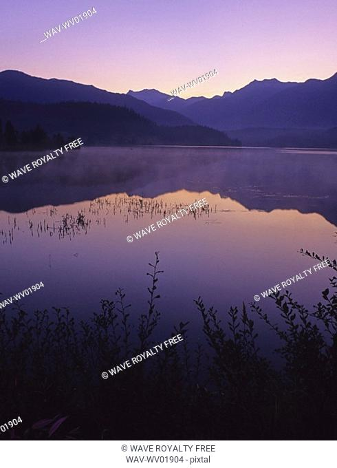 Sunrise glows purple in the reflection, Green Lake, Whistler, BC