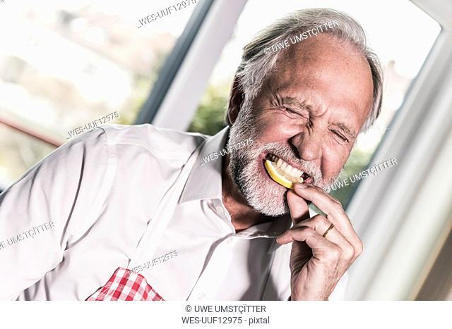 Portrait of man eating lemon slice