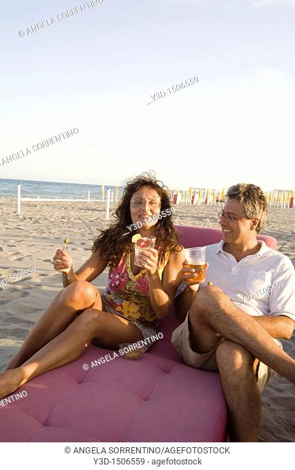 Couple drinking on the beach at sunset