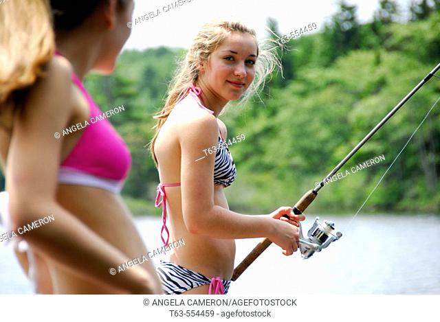 girl 18 looking at girl 13 fishing on dock at cottage