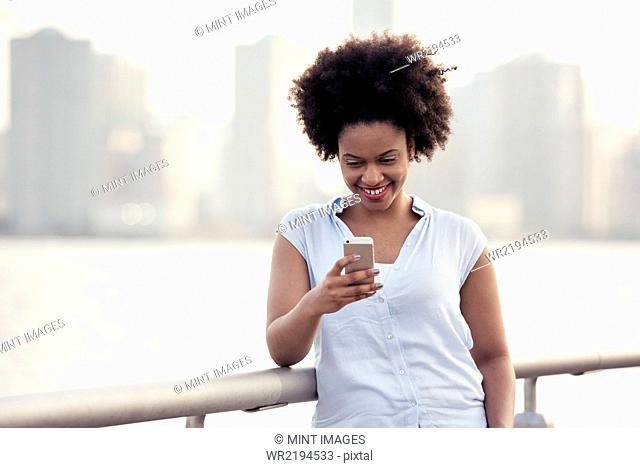 A woman leaning on a waterfront rail checking her cell phone
