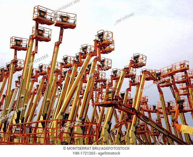 Industrial aerial work platforms facing eachother like getting into a clash with grey sky background in Dordrecht, Zuid Holland, The Netherlands