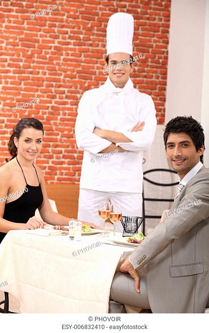 Chef stood with couple in restaurant