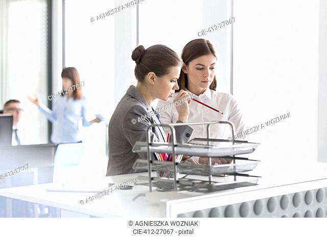 Brunette businesswomen working at laptop in office