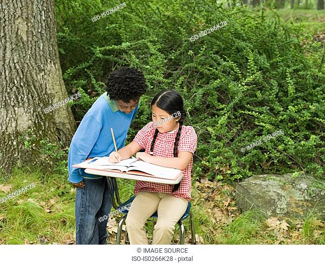 A boy helping his friend with schoolwork