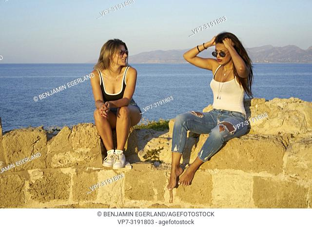 two friends sitting on ancient ruins at seaside, chilling, hanging out, in Chersonissos, Crete, Greece