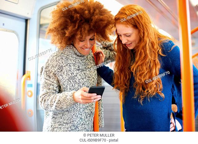 Friends sharing message on mobile phone on train, London