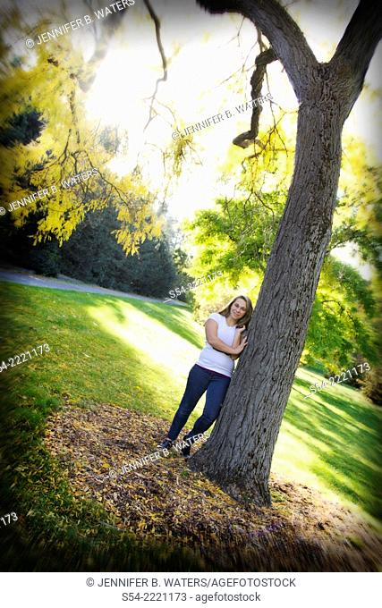 A teen girl leaning against a tree in a park