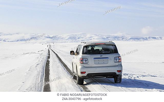 Car driving through a grassland covered in ice and snow in Xinjiang, northen China
