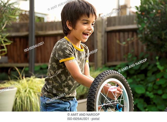 Boy in garden repairing upside down bicycle smiling