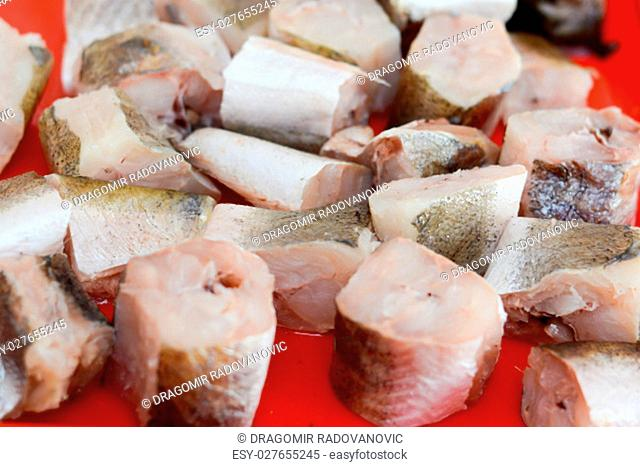 Fish hake sliced and chopped and prepared to be baked on the red plate