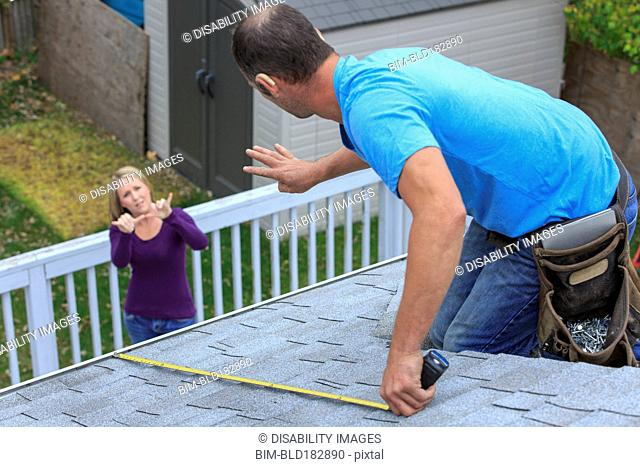 Caucasian homeowner signing to deaf roofer