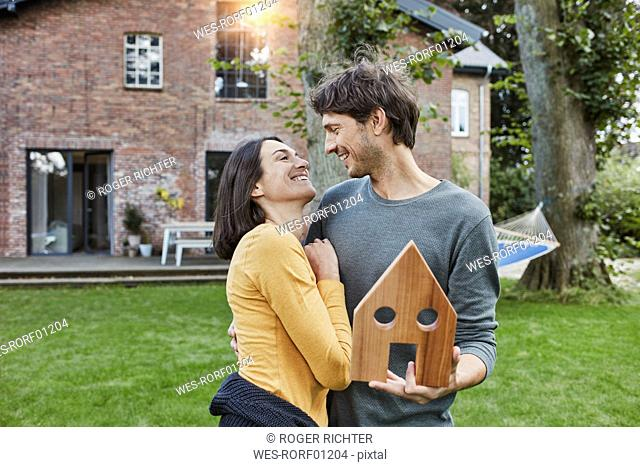 Happy couple in garden of their home holding house model