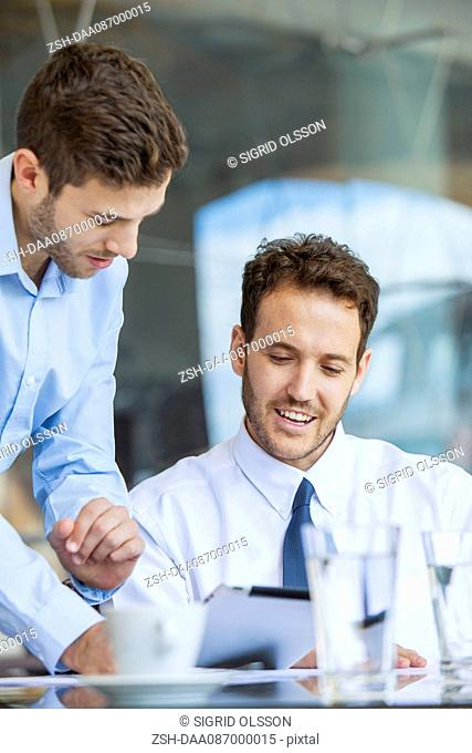Businessman showing proposal to colleague on digital tablet