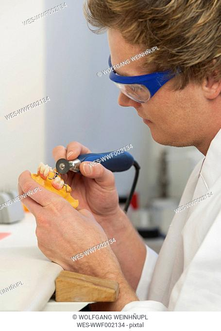 Dentist polishing dentures in dental laboratory