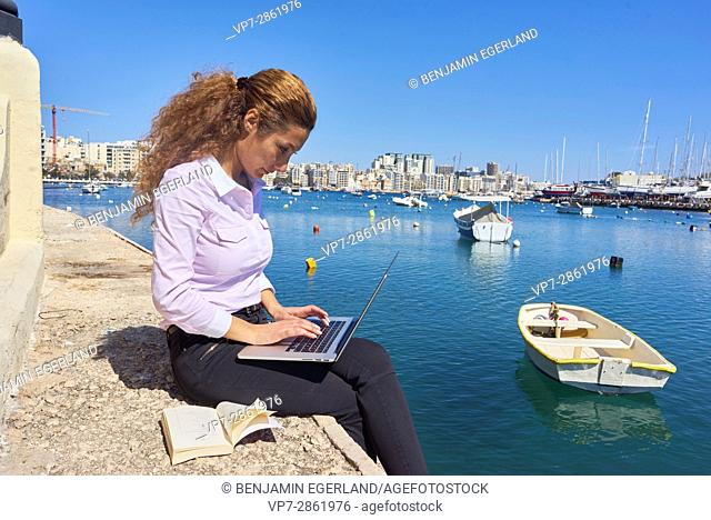 creative business woman working with laptop and book at seaside in holiday destination Gzira, Malta, seeking for inspiration