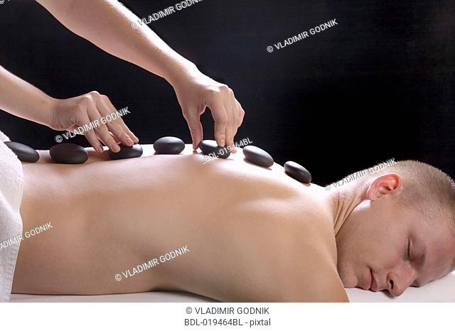 young man getting hot stone massage treatment