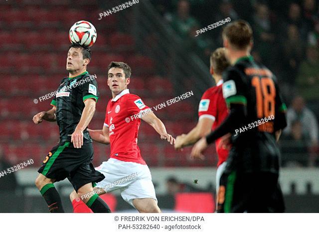Mainz's Stefan Bell (C) and Bremen's Zlatko Junuzovic (L) vie for the ball during the German Bundesliga match between FSVMainz and SVWerder Bremen at Coface...