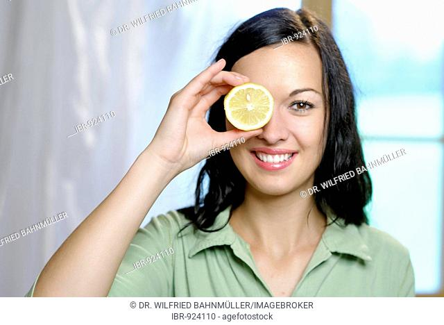 Young women holding a slice of lemon in front of one eye, vitamin C