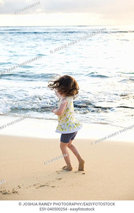 Three year old girl dancing on the beach in Oahu Hawaii while having fun on vacation