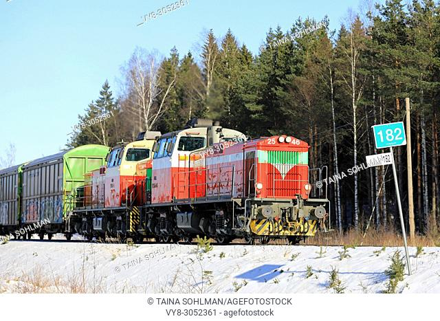 Two diesel engines in front of freight train at speed on sunny day of winter in Raasepori, Finland - March 16, 2018