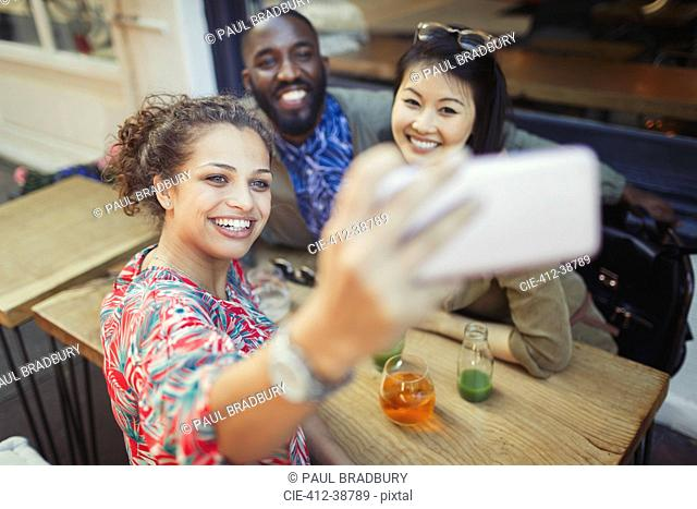 Smiling young friends taking selfie with camera phone at sidewalk cafe