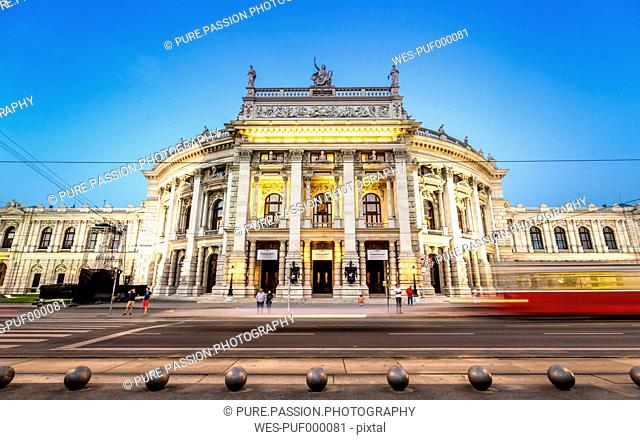 Austria, Vienna, Burgtheater with passing tramway at blue hour