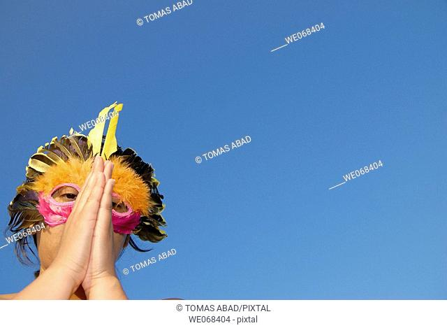 Woman wearing a colored mask resembling a bird. Hands joined as if worshiping-praying