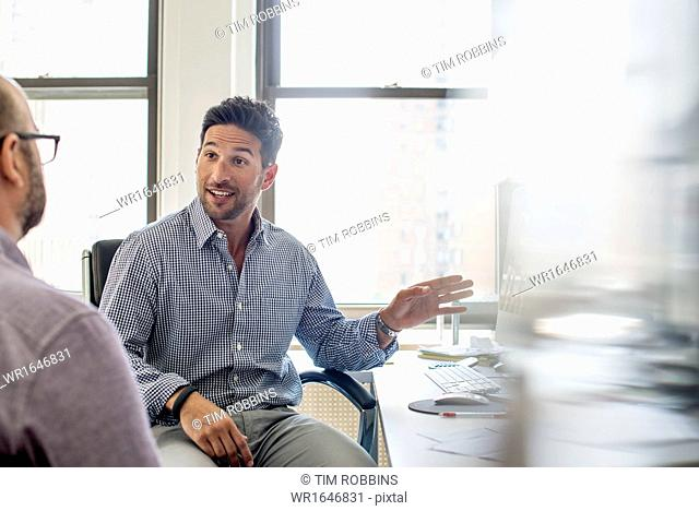 Office life. Two men seated talking and one using his hand to gesture towards a computer monitor